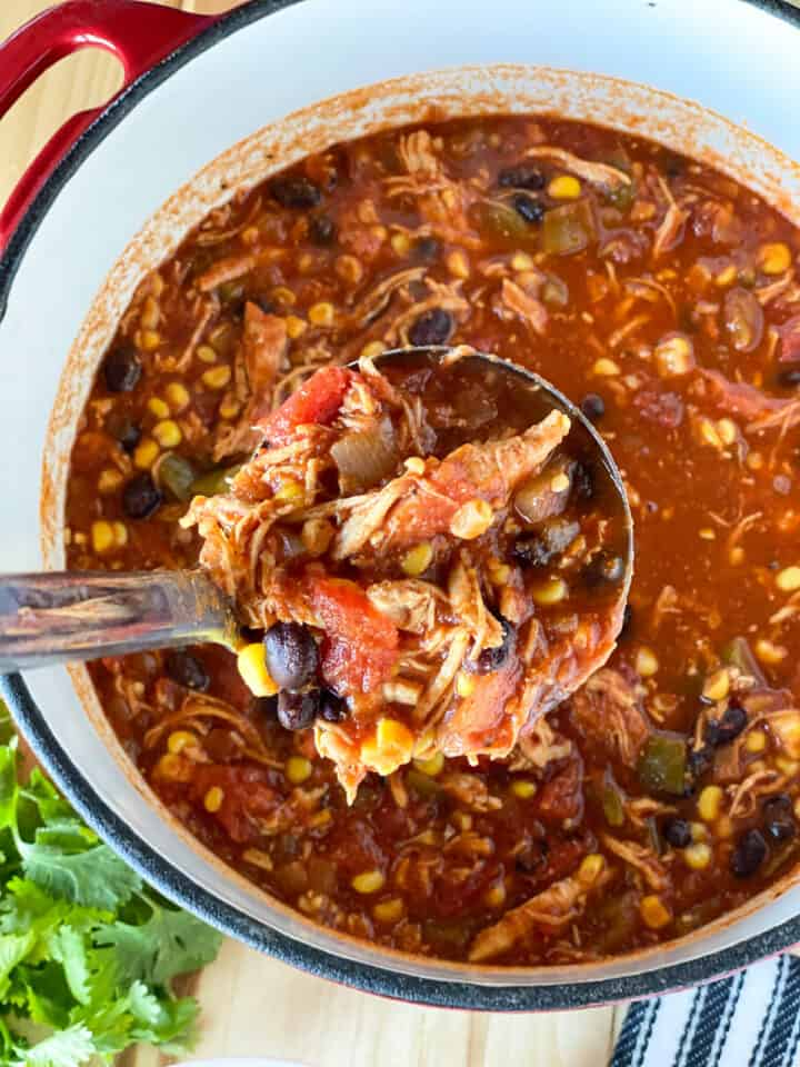Ladleful of easy chicken taco soup out of pot.