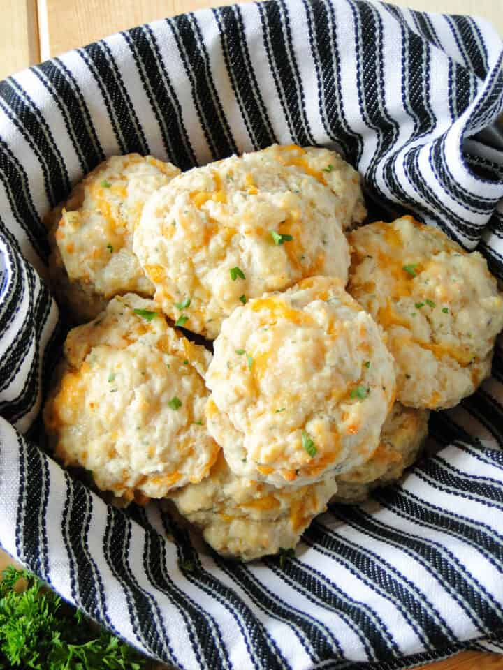 Basket lined with towel full of garlic cheese drop biscuits.