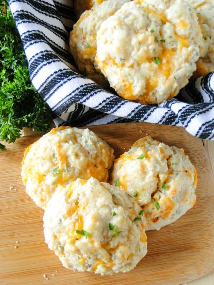 Garlic cheese drop biscuits in basket with towel and 3 biscuits in front of basket.